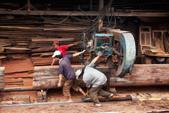 Carpenter pull power-saw at sawmill. QUY NHON, VIE Stock Images