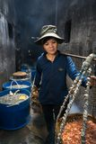 Quy Nhon, Vietnam - Oct 22, 2016: Seafood processing at fish market in Quy Nhon, south Vietnam. A woman carry baskets of boiled se Royalty Free Stock Photo