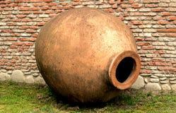 Qvevri —tillbringare för vin-danande på bakgrund för tegelstenvägg Som en amfora arkivfoto