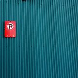 Rà ¹ Œed inget parkeringstecken på ett mörkt - blå zinkvägg royaltyfria bilder