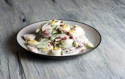 Rábano - pepino - ensalada del huevo de codornices, placa de la porcelana, fondo gris Fotos de archivo