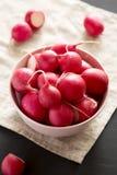 Rábanos rojos frescos en un cuenco rosado, opinión de ángulo bajo Fondo negro fotografía de archivo libre de regalías