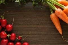Rábanos y zanahorias en una tabla de madera imagenes de archivo