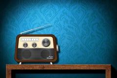 Rádio retro na tabela de madeira com papel de parede azul Fotografia de Stock Royalty Free