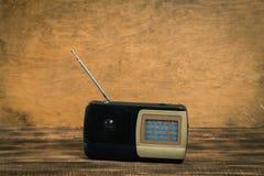 Rádio velho na tabela de madeira com fundo da parede da cor foto de stock
