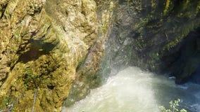 Ráfagas del viento y del agua de la cascada, que establece en las rocas Kmni en la cascada cubierta con el musgo y almacen de video