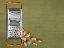 Râpe de nourriture de cuisine avec des clous de girofle d'ail Images libres de droits