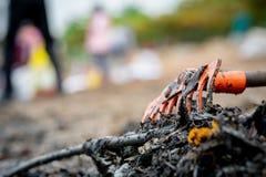 Râteau orange de plan rapproché sur la pile des déchets sales sur le fond brouillé de la plage propre volontaire Pollution enviro photos libres de droits