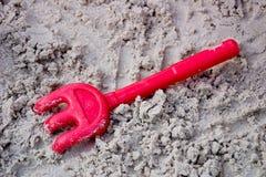Râteau rouge dans le sable Photographie stock libre de droits