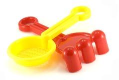 Râteau rouge et jouets jaunes de passoir Photographie stock