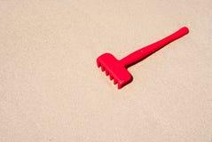 Râteau rouge sur le sable Image libre de droits