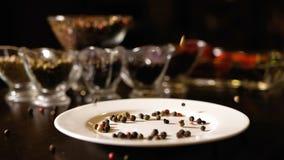 Różni typy peppercorns spadają na białym talerzu Garść pikantność Condiment zbiorników stojak w tle zbiory wideo