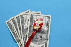 Różnorodne medycyny i pigułki na plastikowej łyżce z pieniądze fotografia royalty free