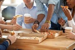 Różnorodni pracownicy je pizzę podczas przerwy na lunch obrazy royalty free