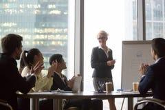 Różnorodni wdzięczni biznesmeni oklaskują głośnikowy gratulowanie z prezentacją zdjęcia stock