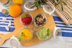 Różnorodny lody smak w słój truskawkowej pistacjowej czekoladowej pomarańcze na drewnianej desce zdjęcie royalty free