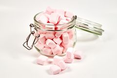 Różowi marshmallows w szklanym słoju na białym tle, obraz royalty free
