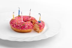 Różowy pączek na bielu talerzu jak urodzinowy tort z świeczkami na białym tle obrazy stock