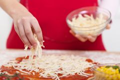 Ręka kropi kraciastego ser na pizzy fotografia royalty free