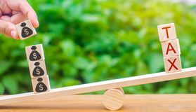 Ręka stawia drewnianych bloki z dolarami na skalach i słowo podatku Pojęcie pomyślna podatek zapłata Długu odpłacenie Rejestr zdjęcia royalty free