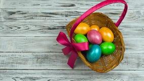 Ręka stawia Wielkanocnego kosz z farbującymi i malującymi jajkami na stole, pojęcie Chrześcijańska uczta Rezurekcyjna Niedziela l zbiory