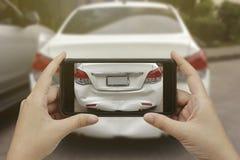 Ręka trzyma mądrze telefon bierze fotografię przy sceną kraksa samochodowa, wypadek samochodowy dla ubezpieczenia obraz stock