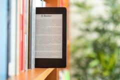 Ręka utrzymuje cyfrową pastylkę w półce na książki w szkolnej bibliotece uczeń fotografia royalty free