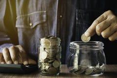 Ręki kładzenia pieniądze moneta w szklanym słoju Oszczędzania pieniądze, pieniężnego i księgowości pojęcie, zdjęcie royalty free