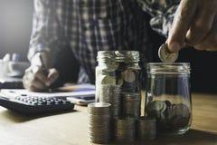 Ręki kładzenia pieniądze moneta w szklanym słoju Oszczędzania pieniądze, pieniężnego i księgowości pojęcie, zdjęcie stock