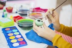 Ręki młoda kobieta malują Wielkanocnych jajka obraz royalty free