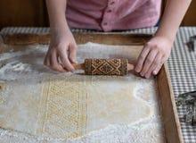 Ręki stacza się ciasto z embossing toczną szpilką na drewnianym tle, obraz royalty free