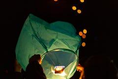 Ręki trzymają zielonego spławowego lampion w górę gdy przygotowywają uwalniać je unosić się w niebo z wiele innymi lampionami zdjęcie royalty free