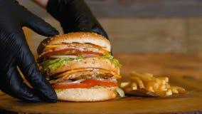 Ręki w czarnych rękawiczkach podnoszą w górę soczystego hamburgeru z dwa warzywami i cutlets Niezdrowy fast food Francuscy dłonia zbiory