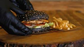 Ręki w rękawiczkach stawiają soczystego czarnego hamburger z dużymi warzywami na drewnianej desce i cutlets obok francuskich dłon zbiory