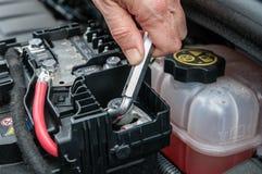 Räcka åtdragning av en klämma av en bilmotor med en skiftnyckel arkivfoto
