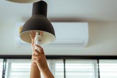 Räcka att ändra med den nya LEDDE ljusa kulan för lampan, maktbesparingbegrepp royaltyfria bilder