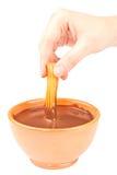 Räcka att doppa en Churro i choklad Royaltyfri Foto