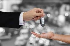 Räcka att ge och att motta bilen den nyckel- fjärrkontrollen med Bokeh av bakgrund för biltrafik Royaltyfria Bilder