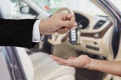 Räcka att ge och att motta bilen den nyckel- fjärrkontrollen, med modern bilbakgrund Royaltyfria Bilder