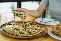 Räcka att gripa ett stycke av spenat- och getostpizza på ett trä royaltyfri fotografi