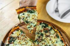 Räcka att gripa ett stycke av spenat- och getostpizza på trätabellen arkivbild