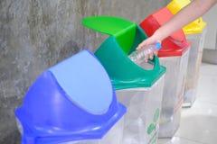 Räcka att kasta den tomma plast- flaskan in i avfallet fotografering för bildbyråer