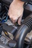 Räcka att kontrollera det olje- locket av en bilmotor royaltyfri bild