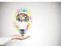 Räcka att rymma en ljus kula med en hjärna för ljus kula Royaltyfria Foton