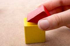 Räcka att rymma ett hus bildat ut ur byggnadskvarter royaltyfri bild