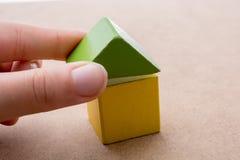 Räcka att rymma ett hus bildat ut ur byggnadskvarter royaltyfria bilder