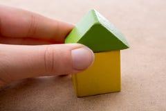 Räcka att rymma ett hus bildat ut ur byggnadskvarter royaltyfria foton