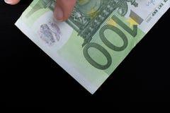 Räcka att rymma sedeln för euro 100 på en svart bakgrund Arkivbild