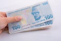 Räcka att rymma 100 Turksh Lirasedlar i hand Royaltyfri Foto