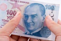 Räcka att rymma 100 Turksh Lirasedlar i hand Fotografering för Bildbyråer